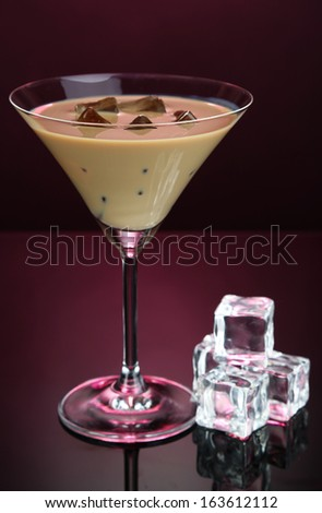Baileys liqueur in glass on pink background - stock photo