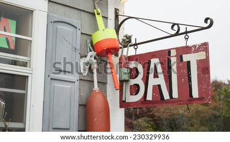 Bait shop sign hang from wall with fishing buoys. - stock photo