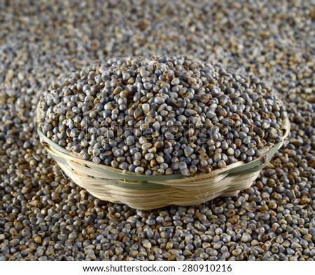 Bajra (Pearl millet) in wooden (bamboo) basket - stock photo