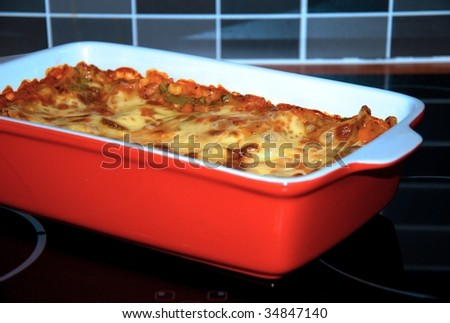 Bake lasagne in the red saucer. - stock photo
