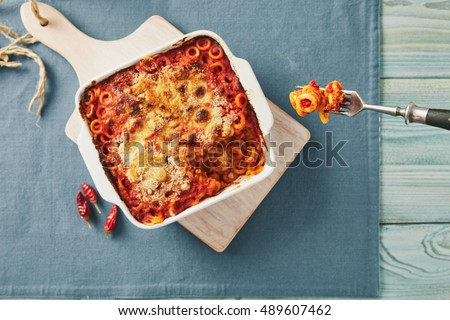 Baked anelletti pasta with mince, sauce and mozzarella. Typical sicilian dish