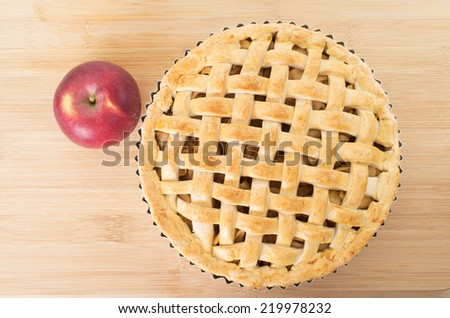 Baked apple pie against wooden background - stock photo