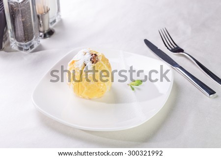 Baked apple stuffed with dried fruit, nuts on plate - stock photo