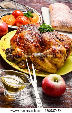 Baked apples chicken with vegetable garnish on wooden background - stock photo