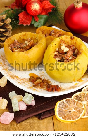 Baked apples on plate on wooden table