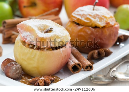 baked apples stuffed with dried fruit, nuts and cottage cheese on plate, close-up, horizontal - stock photo