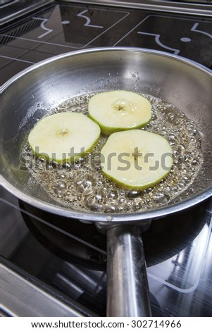 Baked apples with cinnamon on a frying pan - stock photo
