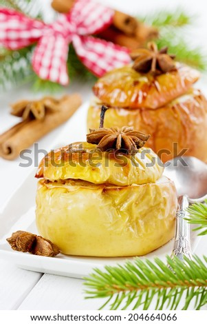 baked apples with honey, curds, raisins and nuts in a white plate decorated pine branches, cinnamon sticks and anise star on a wooden background