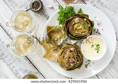 Baked artichokes cooked with garlic sauce, mustard and parsley. Top view - stock photo