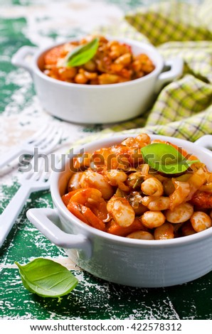 Baked beans in sauce with vegetables in rustic style. Selective focus.