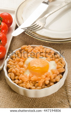 baked beans with fried egg in a round, small serving plate - stock photo