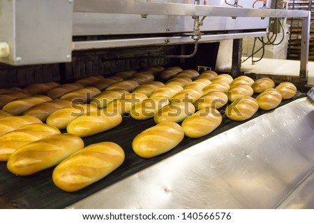 Baked Breads on production line at bakery - stock photo