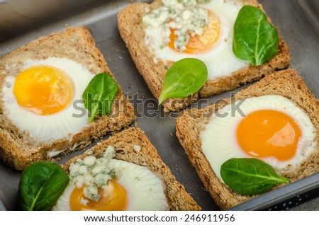 Baked Bull's-Eye Eggs on whole wheat toast with spinach and blue cheese on top - stock photo