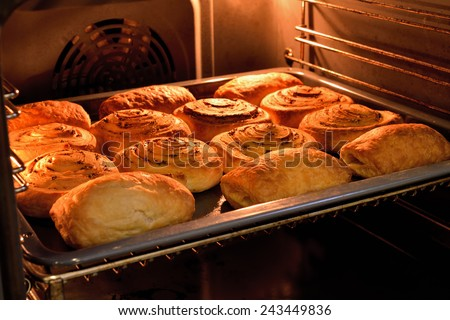 Baked cakes on a tray in the oven. - stock photo