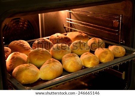 Baked cakes on a tray in the oven - stock photo
