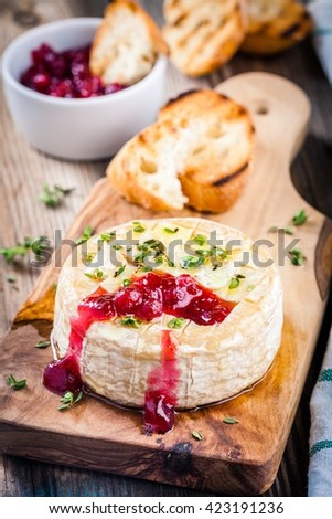 Baked camembert with cranberry sauce and thyme on rustic wooden table