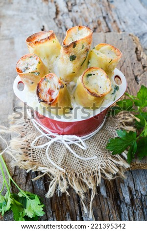 baked cannelloni on old boards. Delicious dinner. - stock photo
