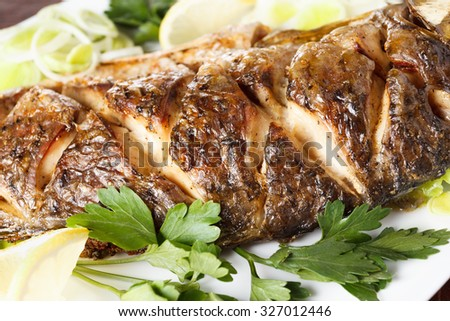 Baked carp fish with vegetables entirely. Traditional Christmas meal. Closeup - stock photo