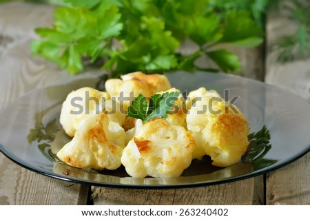 Baked cauliflower on glass plate over wooden table, close up view - stock photo