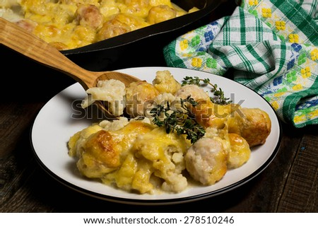 Baked cauliflower with meatballs and cheese in a baking tray and plate, green cloth on a wooden background - stock photo