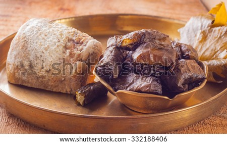 Baked cheese in vine leaves in copper bowl on a copper pan on a wooden table, horizontal - stock photo