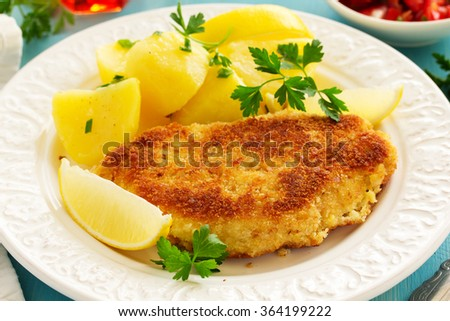 Baked chicken breast with a crispy crust, served with boiled potatoes. - stock photo