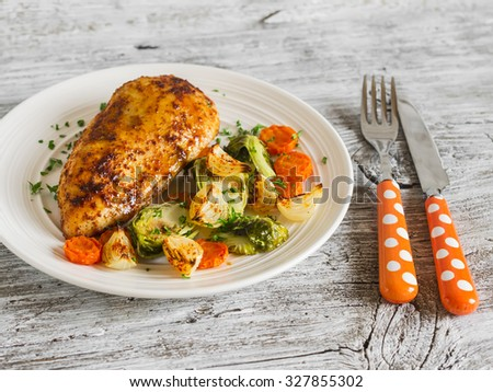 baked chicken breast with brussels sprouts, onions and carrots on a white plate on wooden surface. Healthy food - stock photo