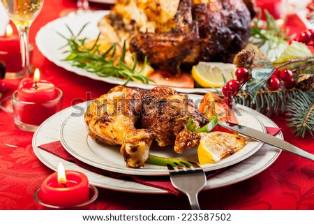 Baked chicken for Christmas dinner on festive table - stock photo