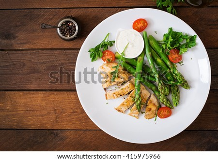 Baked chicken garnished with asparagus and tomatoes. Top view - stock photo