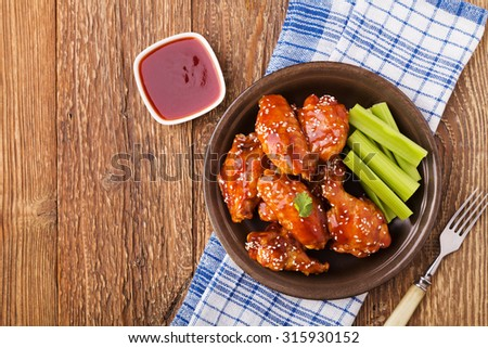 Baked chicken wings in honey sauce sprinkled with sesame seeds. - stock photo