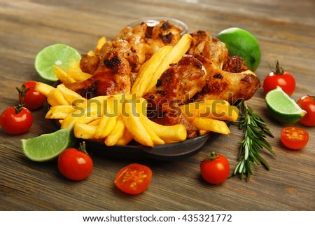 Baked chicken wings with French fries on wooden table - stock photo