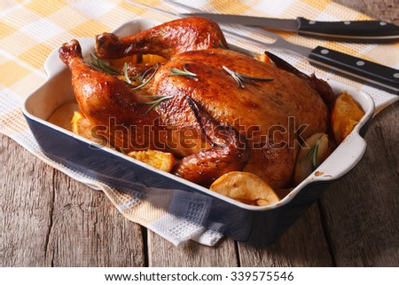 baked chicken with apples in the baking dish on a table close-up. horizontal - stock photo