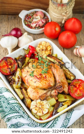 Baked chicken with vegetables and herbs. Dinner in a rustic style. Selective focus - stock photo