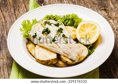 Baked cod fillet on rustic potato pillow - stock photo