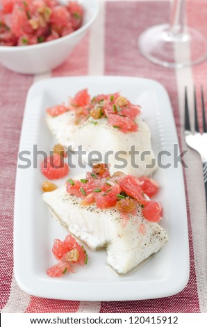 Baked cod with grapefruit salsa on white dish closeup