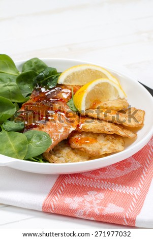 Baked coho salmon, rice pancakes, lemon and young spinach leaves - stock photo