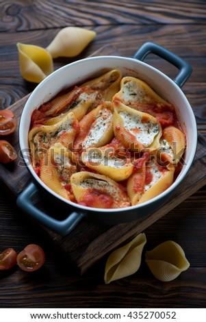 Baked conchiglioni with cottage cheese stuffing, selective focus