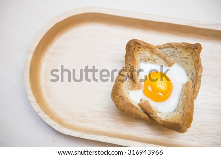 baked egg in bread bowl on wooden tray, food