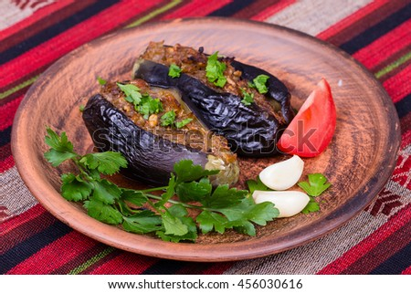 Baked eggplant stuffed with onions, cherry plums and walnuts on the plate, close up - stock photo