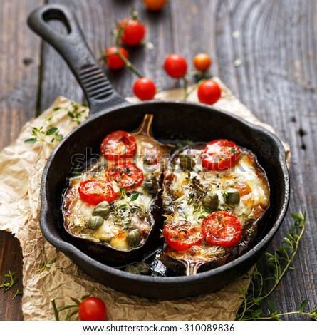 Baked eggplant stuffed with vegetables and mozzarella cheese with addition aromatic herbs. Delicious vegetarian dish - stock photo