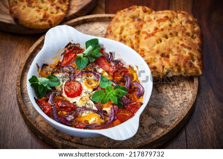 Baked feta cheese with vegetables and olive bread - stock photo