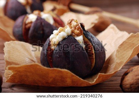 baked figs with goat cheese,walnuts and honey in paper baskets on wooden table - stock photo