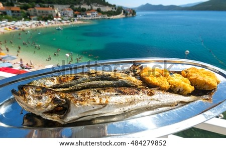 Baked fish with a outstanding blue sea view