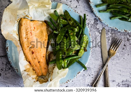 Baked fish with beans on rustic background - stock photo