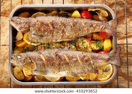 Baked fish with roasted potatoes in metal bowl