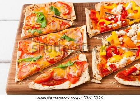 Baked flat bread with bell peppers and feta cheese and also with ham, tomatoes and cheese. selective focus - stock photo