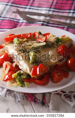 Baked Flounder with peppers and broccoli close-up on a plate on the table. vertical