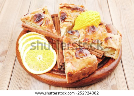 baked food : apple pie cuts on over table with cinnamon sticks and lemons - stock photo
