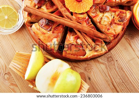 baked food : apple pie served with fresh apples, raw lemon and mandarin,  tea cup on wooden plate over table - stock photo