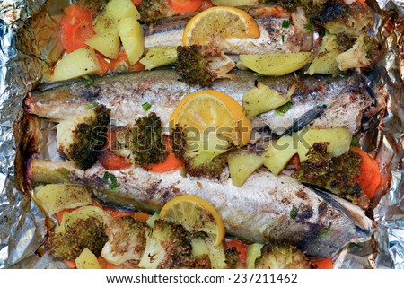 Baked fresh fish and vegetables in casserole with foil - stock photo